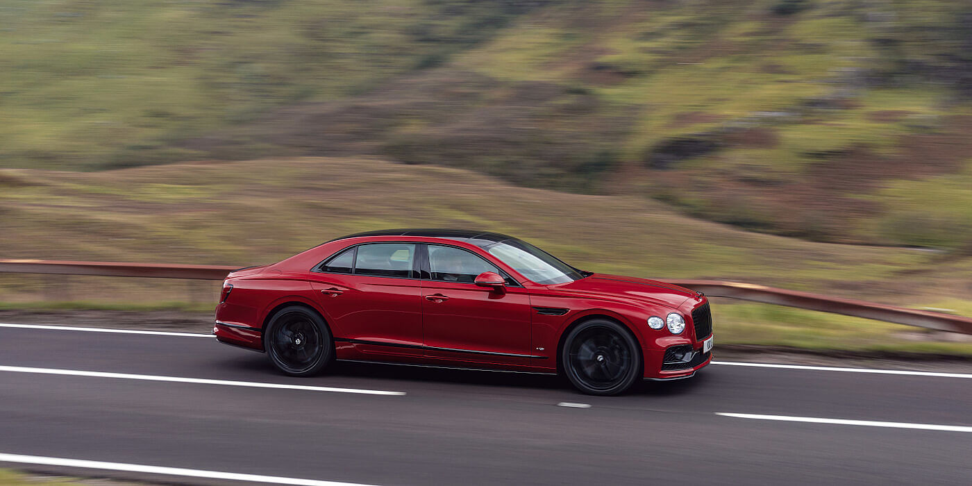 new-Bentley-Flying-Spur-V8-in-Dragon-Red-2-paint-colour-driving-on-mountain-road-in-Scotland-profile-view